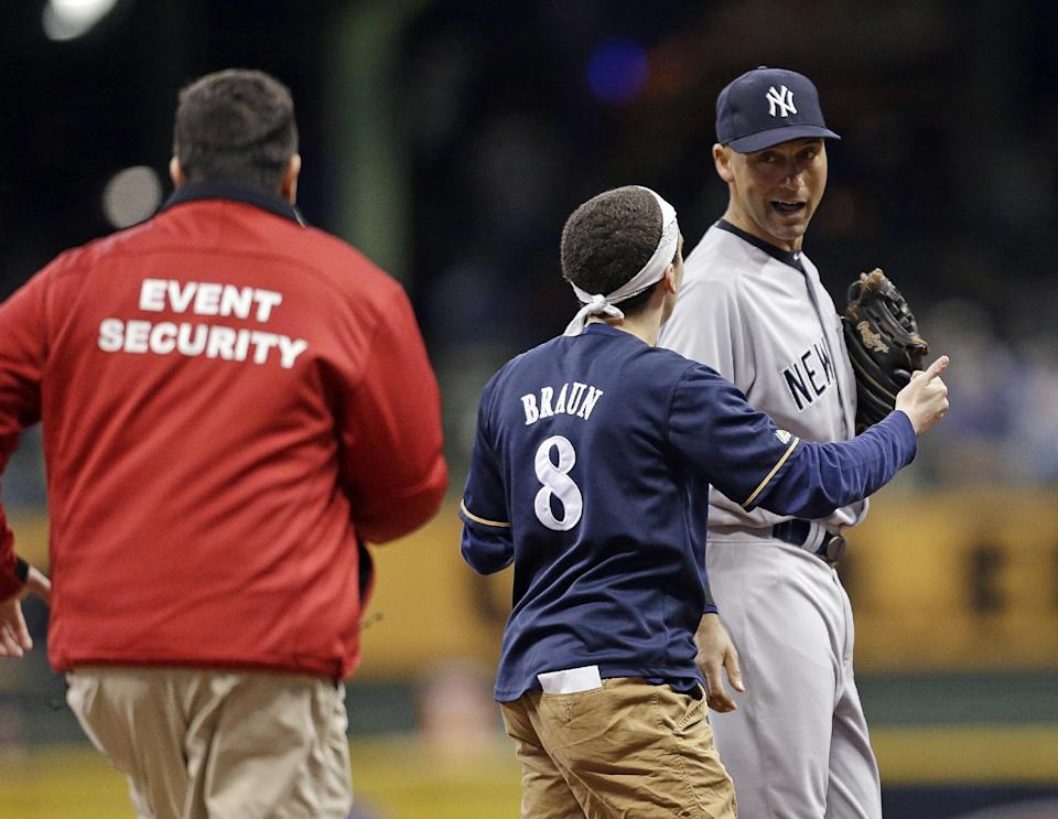A fan runs out on the field to New York Yankees' Derek Jeter, right, in the sixth inning of a baseball game against the Milwaukee Brewers, Friday, May 9, 2014, in Milwaukee. (AP Photo/Jeffrey Phelps)