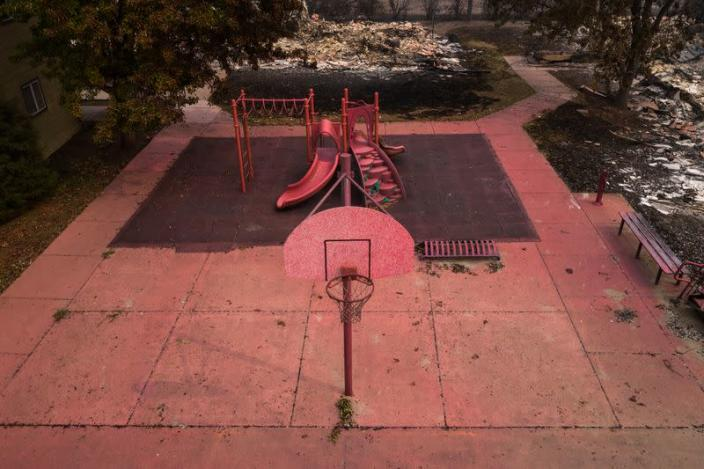 Red fire retardant blankets basketball post and a playground in the aftermath of the Almeda fire in Talent, Oregon