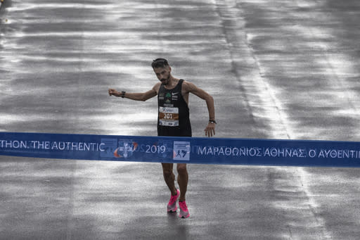 Greek marathon runner Costas Gelaouzos finishes at the third place of the 37th Athens Marathon on Sunday, Nov, 10, 2019. John Kipkorir Komen, of Kenya, a 42-year-old runner finished first in a time of 2 hours, 16 minutes, 34 seconds, beating second Rwanda's Felicien Muhitira, 17 years his junior, by nine seconds. (AP Photo/Yorgos Karahalis)