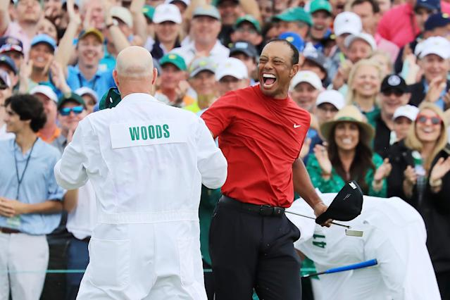 Tiger Woods (R) of the United States celebrates with caddie Joe LaCava (L) on the 18th green after winning during the final round of the Masters at Augusta National Golf Club on April 14, 2019 in Augusta, Georgia. (Photo by David Cannon/Getty Images)