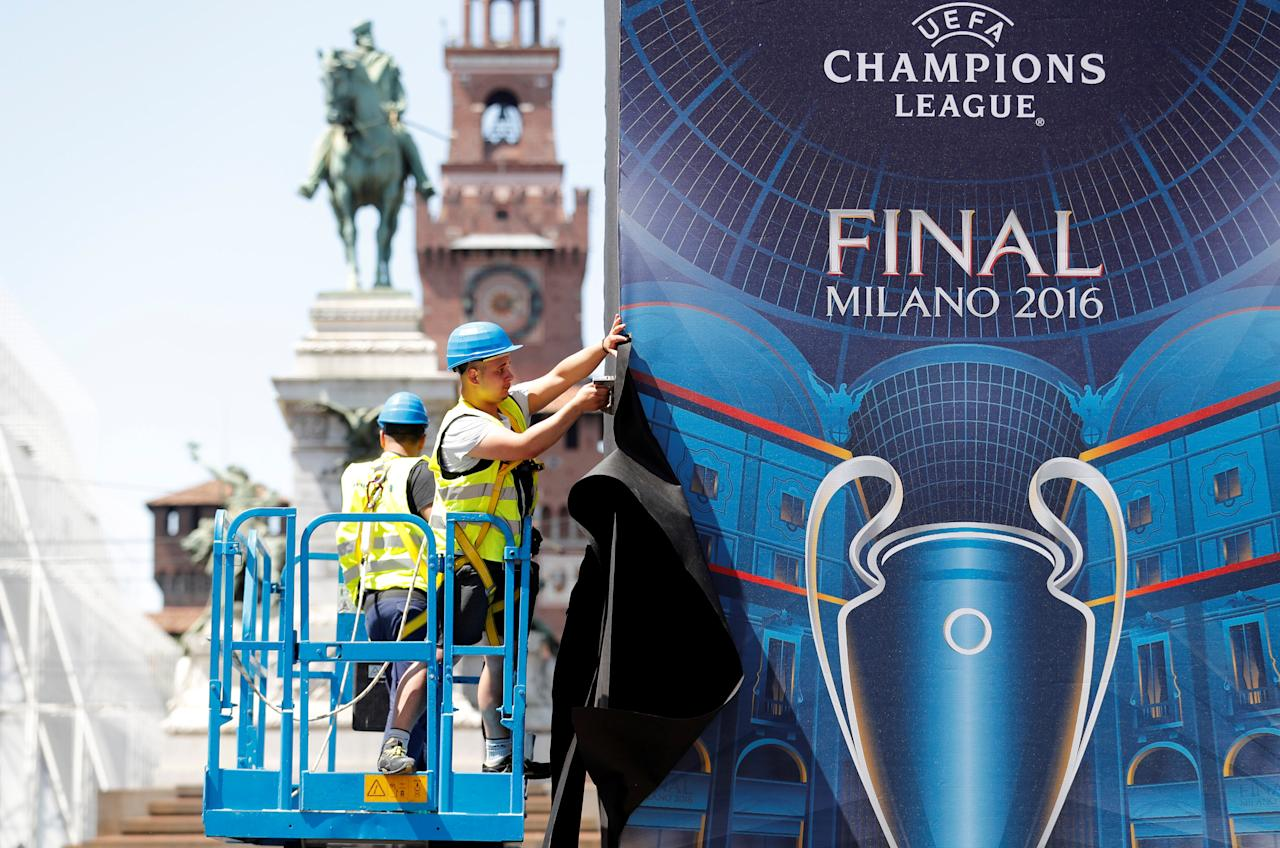 Workers set a banner of the UEFA Champions League Final 2016 downtown Milan, Italy, May 24, 2016. REUTERS/Stefano Rellandini
