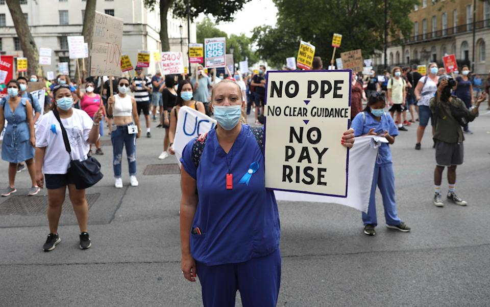 NHS (National Health Service) workers hold placards as they protest outside Downing Street during a march through the streets of London on August 8, 2020, to demand a pay rise. (Photo by ISABEL INFANTES / AFP) (Photo by ISABEL INFANTES/AFP via Getty Images)