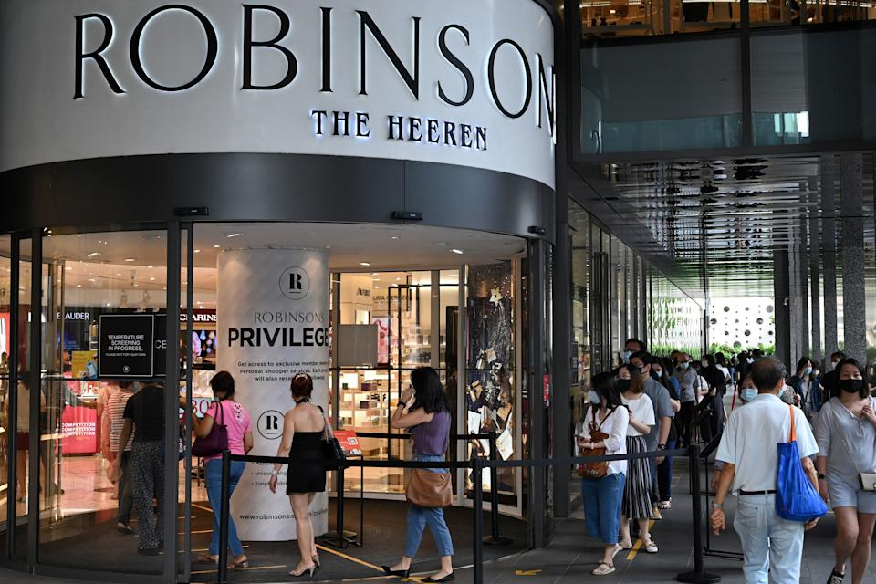 Customers queue to enter a Robinsons department store at the Hereen in the Orchard Road shopping belt in Singapore on October 30, 2020, after the company announced that it was closing its last two stores in the country due to falling demand as more consumers shift to online shopping. (Photo by Roslan RAHMAN / AFP) (Photo by ROSLAN RAHMAN/AFP via Getty Images)