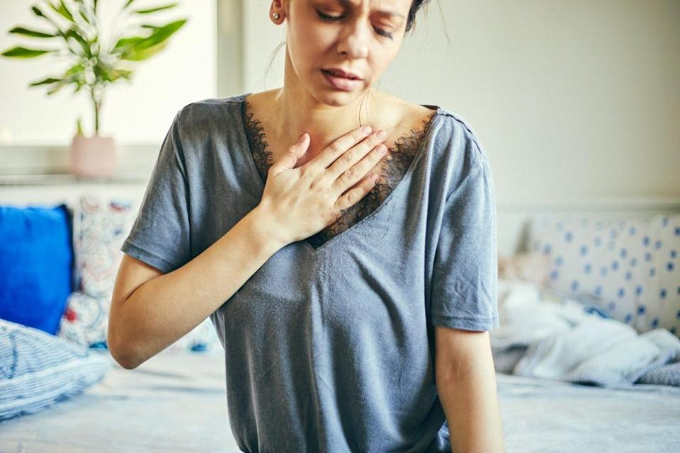 woman suffering from chest pain while sitting at home