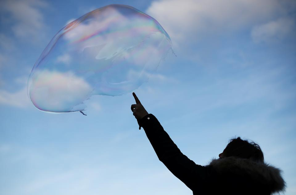 A woman bursts a large soap bubble as it floats through the air in central London, Britain, December 27, 2019. REUTERS/Hannah McKay