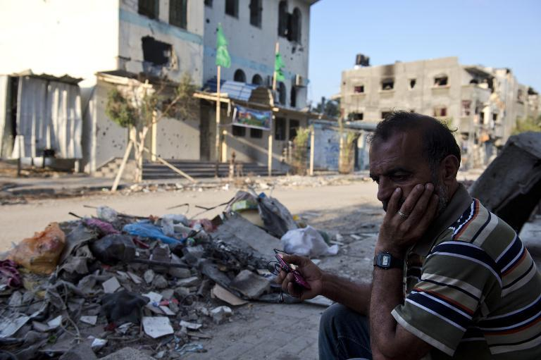 Abu Naael, a Palestinian man living with his family in his partly destroyed home in the Shejaiya neighborhood of Gaza City, listens to the radio on his mobile phone on August 18, 2014
