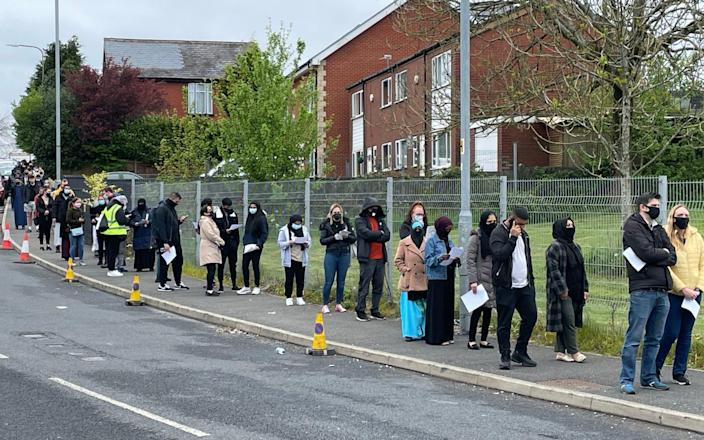 People queue for the vaccination centre at the Essa Academy in Bolton. - PA