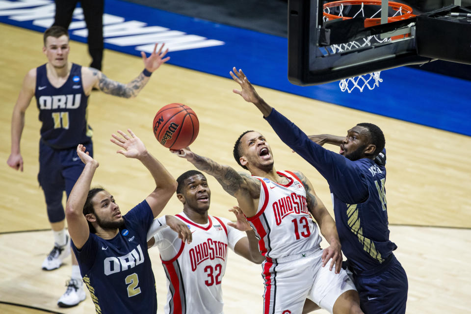 Ohio State's CJ Walker (13) drives in for a layup against Oral Roberts' DeShang Weaver, right, during the second half of a first-round game in the NCAA men's college basketball tournament, Friday, March 19, 2021, at Mackey Arena in West Lafayette, Ind. Oral Roberts won in overtime. (AP Photo/Robert Franklin)