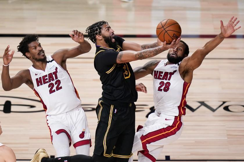 Los Angeles Lakers forward Anthony Davis shoots between Miami Heat forward Jimmy Butler.