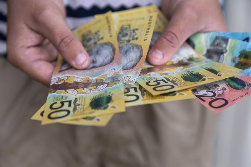 Male person holding some Australian currency. This visual concept evokes ideas around saving money, paying for expenses and investments.