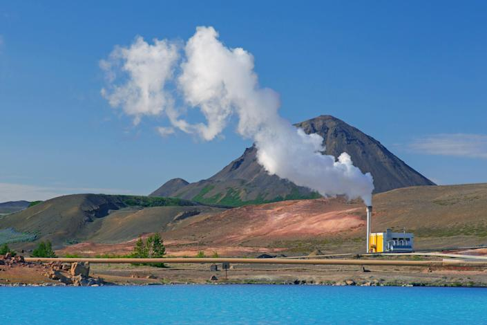 lots of steam arises from a geothermal power station located along water. There's a mountain in the background