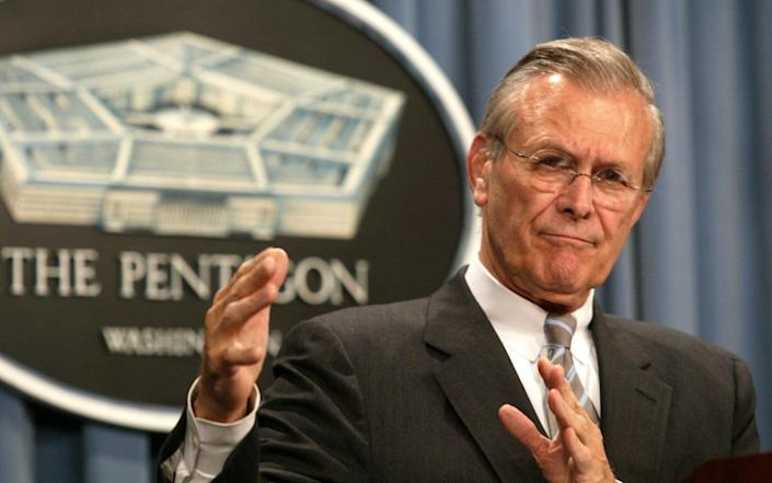 Donald Rumsfeld gestures during a press conference at the Pentagon