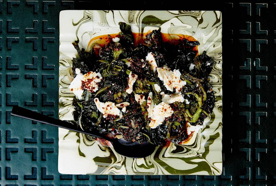 """Also known as the """"cooked to hell"""" method, this braise renders the greens meltingly tender. If you can't find Aleppo, use 1½ tsp. crushed red pepper flakes instead. <a href=""""https://www.bonappetit.com/recipe/braised-greens-with-aleppo-oil-and-feta?mbid=synd_yahoo_rss"""" rel=""""nofollow noopener"""" target=""""_blank"""" data-ylk=""""slk:See recipe."""" class=""""link rapid-noclick-resp"""">See recipe.</a>"""