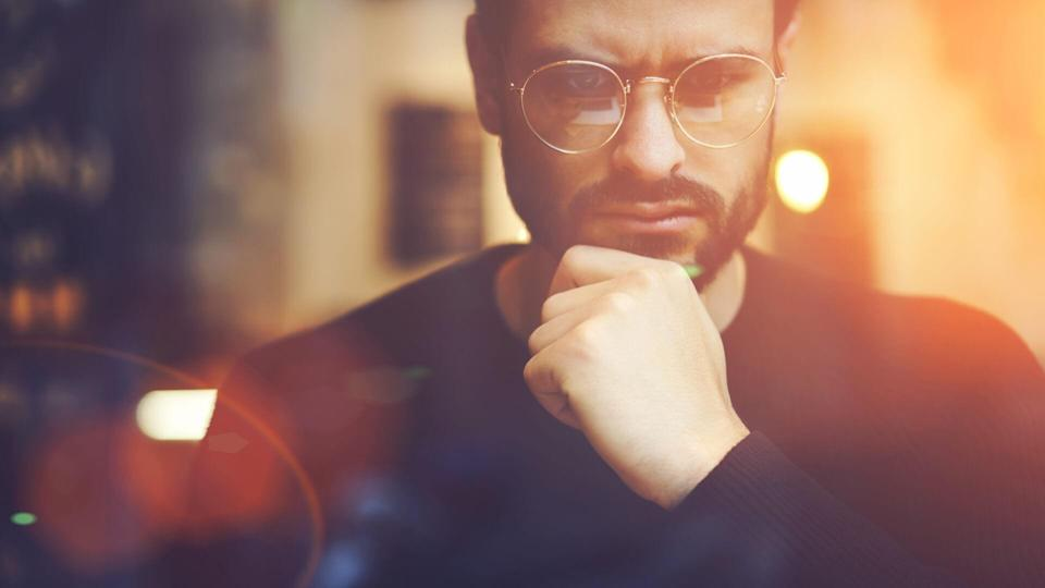 Cropped close up image of pensive bearded entrepreneur in optical spectacles for better views dressed in black sweatshirt.