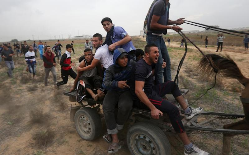 Palestinian protesters carry an injured comrade during clashes with Israeli security forces near Shejaiya, an eastern district of Gaza City, on November 6, 2015 (AFP Photo/Mahmud Hams)