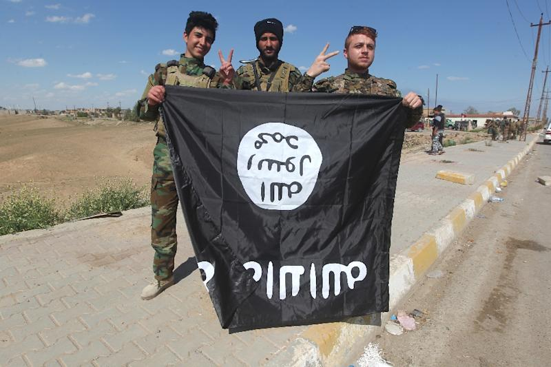 Iraqi Sunni and Shiite fighters pose for a photo with an Islamic State (IS) group flag in Al-Alam, northeast of the Iraqi city of Tikrit, on March 17, 2015 after recapturing the town from IS fighters (AFP Photo/Ahmad al-Rubaye)