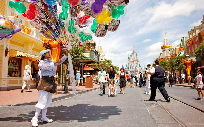 Woman holding balloons in Disney world
