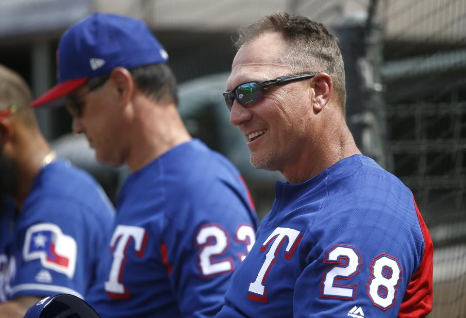In this March 8, 2018 photo Texas Rangers manager Jeff Banister (28) and bench coach Don Wakamatsu (23) sit on the field watching the Rangers during the second inning of a spring training baseball game against the Chicago White Sox in Surprise, Ariz. Rangers general manager Jon Daniels anticipates interviewing at least five to eight candidates in his search for the teams new manager. The Rangers fired Banister with 10 games left in the season. They finished last in the AL West. (AP Photo/Ross D. Franklin)