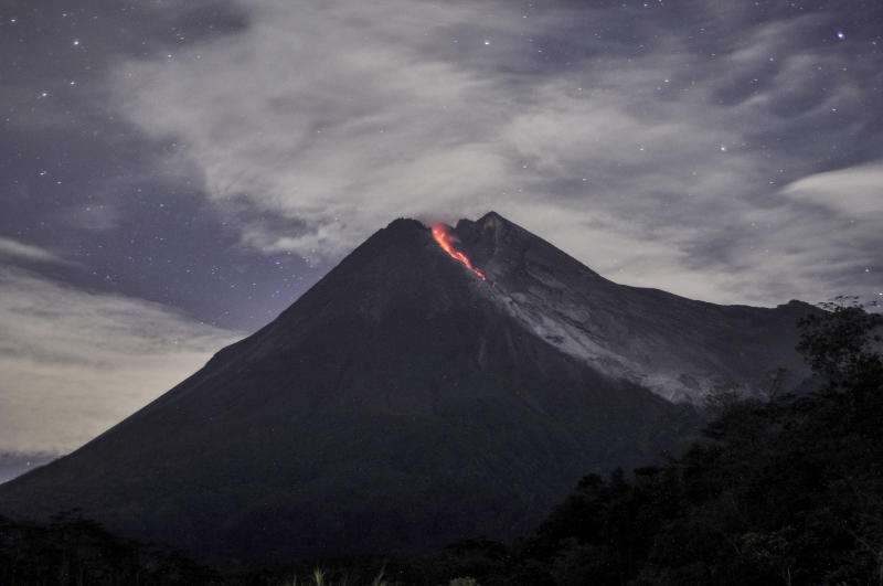 In this Tuesday, Jan, 29, 2019, photo. Mount Merapi spews volcanic material as it erupts as seen from Cangkringan, Yogyakarta, Indonesia. Indonesia's most volatile volcano has unleashed a 1,400 meters (4,600 feet) dark red volcanic material 1,400 meters (1,500 yards) down the slopes. (AP Photo/Slamet Riyadi)