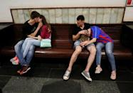 People wait for the train at a metro station after a World Cup soccer match in Moscow, Russia July 1, 2018. REUTERS/Gleb Garanich