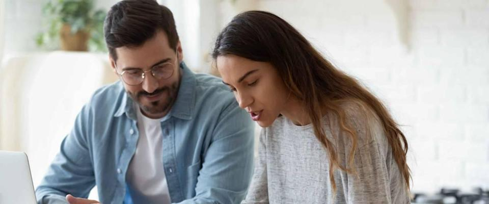 Young couple looking down at calculator while managing finances at kitchen table.