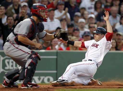 Boston Red Sox's Daniel Nava, right, scores on a hit by Dustin Pedroia as Atlanta Braves' David Ross waits for the throw in the second inning of a baseball game in Boston, Saturday, June 23, 2012. (AP Photo/Michael Dwyer)