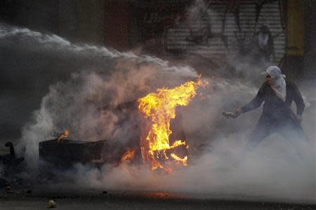 An anti-government protester tries to set fire to a barricade while up against the police's water canon during clashes in Caracas