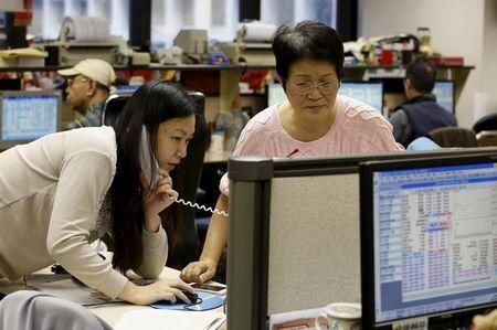 Broker takes order beside her colleague during afternoon trading at a brokerage in Hong Kong