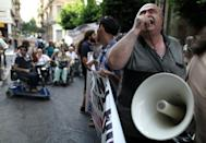 A disabled man chants slogans using a loudspeaker, outside the Finance Ministry in Athens, on Thursday, Sept. 13, 2012. Disabled groups are angry at likely benefit cuts under a major new austerity program demanded by international rescue creditors. (AP Photo/Petros Giannakouris)