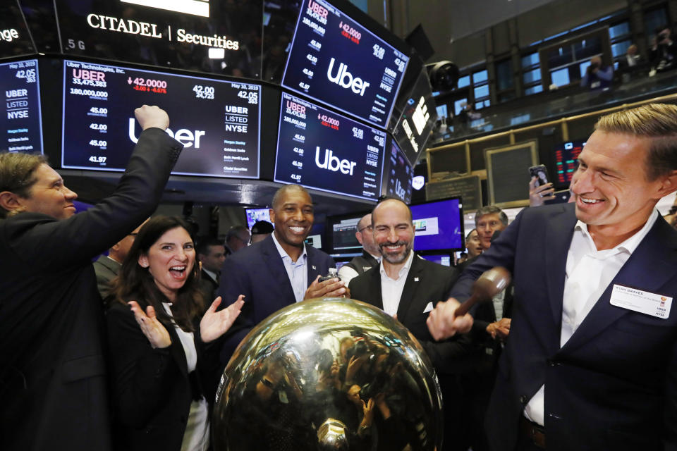FILE - In this Friday, May 10, 2019 file photo, Uber board member Ryan Graves, right, rings a ceremonial bell as the company's stock opens for trading during its initial public offering at the New York Stock Exchange. Stacey Cunningham, second from left, president of the NYSE, Tony West, center, Uber's Chief Legal Officer, and CEO Dara Khosrowshahi, second from right, applaud. A fare war between Uber and Lyft has led to billions of dollars in losses for both ride-hailing companies as they fight for passengers and drivers. But in one way it has been good for investors who snatched up the newly public companies' stock: The losses have scared off the competition, giving the leaders a duopoly in almost every American city. (AP Photo/Richard Drew)