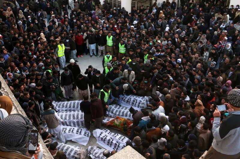 People and family members gather to identify the bodies of their relatives, who were coal miners and got killed by unidentifyed persons in Mach area of Bolan district, in Quetta,