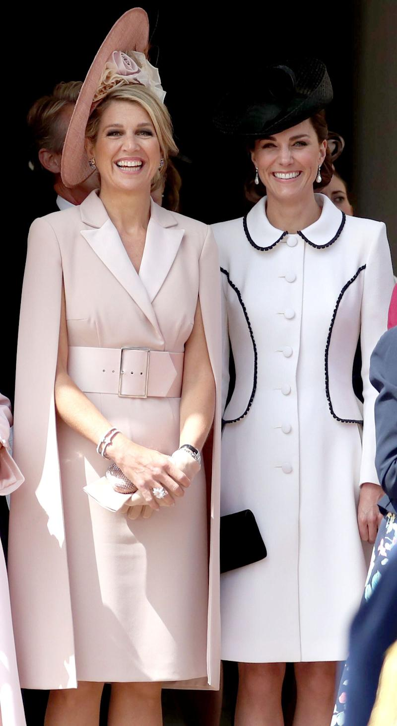 The Netherlands' Queen Maxima and Catherine, Duchess of Cambridge watch the procession to St. George's Chapel. (Photo: STEVE PARSONS via Getty Images)