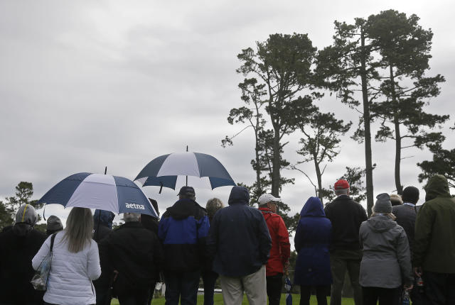 Fans hold umbrellas in the rain on the 18th green of the Spyglass Hill Golf Course during the second round of the AT&T Pebble Beach Pro-Am golf tournament Friday, Feb. 8, 2019, in Pebble Beach, Calif. (AP Photo/Eric Risberg)