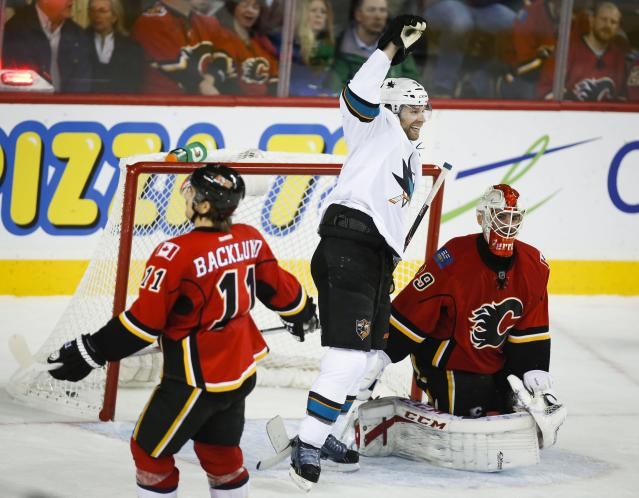 San Jose Sharks' Brad Stuart, center, celebrates his game-winning goal as Calgary Flames goalie Reto Berra, right, from Switzerland, looks away and Mikael Backlund, from Sweden, skates away during overtime in an NHL hockey game in Calgary, Alberta, Tuesday, Nov. 12, 2013. The Sharks won 3-2. (AP Photo/The Canadian Press, Jeff McIntosh)