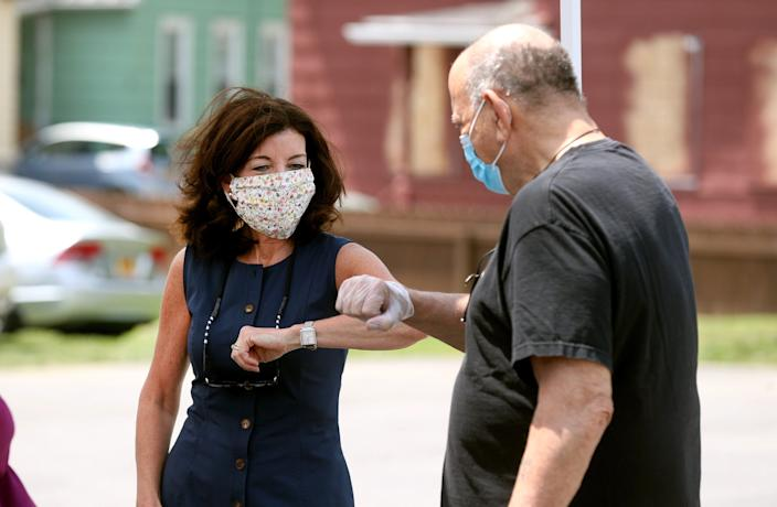 New York Lt. Gov. Kathy Hochul taps elbows to greet Don Agostinelli outside El Pilon  Criollo restaurant in Rochester, N.Y. Agostinelli's business, Clinton Ave Jewelry and Pawn, was vandalized during unrest after a Black Lives Matter rally May 30.