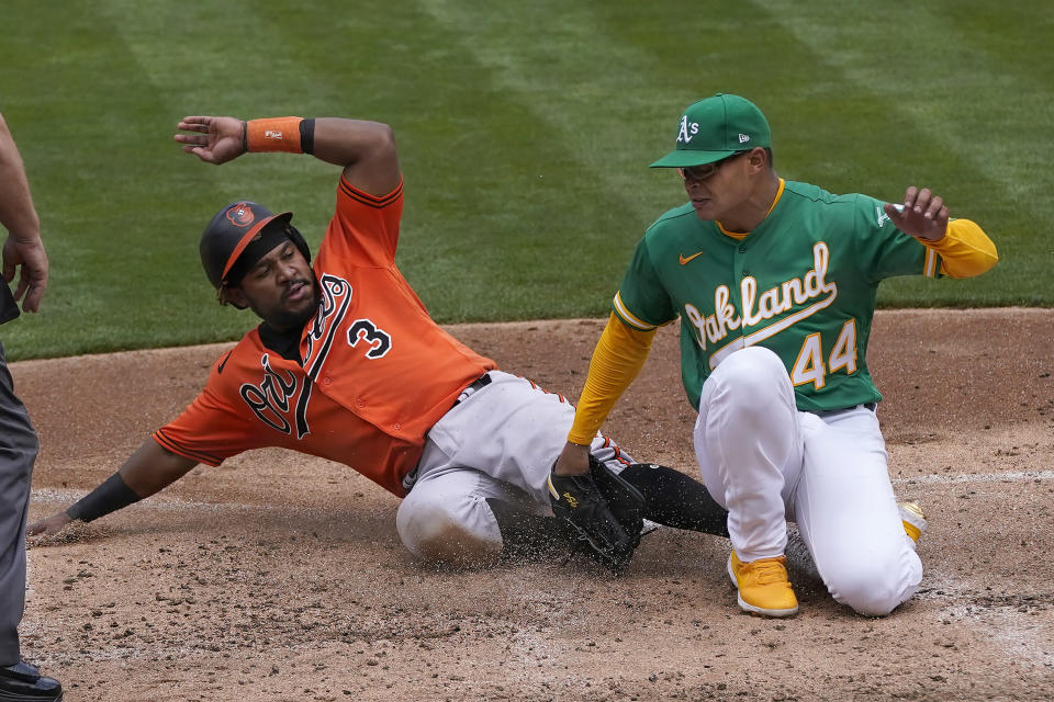 Baltimore Orioles' Maikel Franco (3) slides home to score against Oakland Athletics pitcher Jesus Luzardo (44) during the third inning of a baseball game in Oakland, Calif., Saturday, May 1, 2021. (AP Photo/Jeff Chiu)