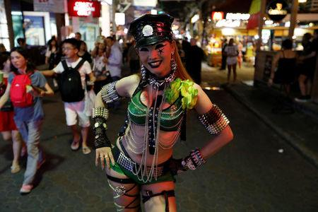 A woman promotes a go-go dance bar in Pattaya