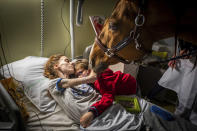 In this image released by World Press Photo, Thursday April 15, 2021, by Jeremy Lempin, Divergence-Images, titled Doctor Peyo and Mister Hassen, which won second prize in the Contemporary Issues category, shows Marion (24), who has metastatic cancer, embraces her son Ethan (7) in the presence of Peyo, a horse used in animal-assisted therapy, in the Selene Palliative Care Unit at the Centre Hospitalier de Calais, in Calais, France, on 30 November 2020. (Jeremy Lempin, Divergence-Images, World Press Photo via AP)