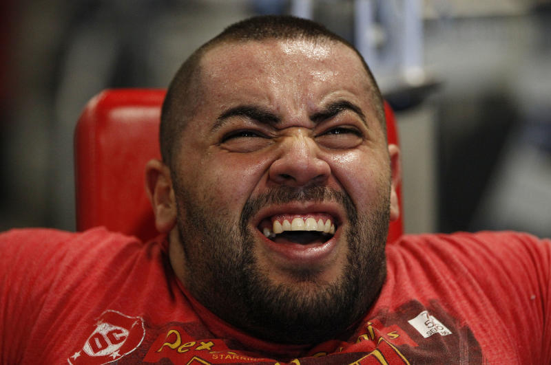 In this photo taken, Friday, Nov. 16, 2012, Egyptian Body builder Moustafa Ismail grimaces during his daily workout at World Gym in Milford, Mass. Ismail has been given the title of world's biggest arms, biceps and triceps, by the Guinness Book of World Records. (AP Photo/Stephan Savoia)