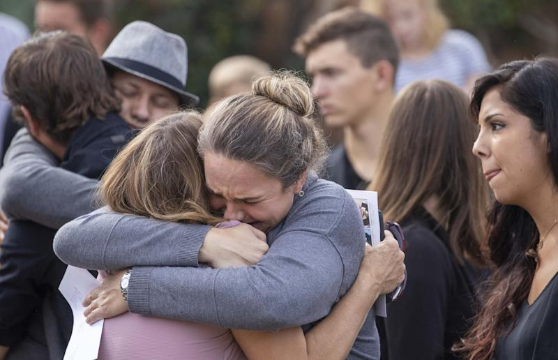Family members and friends console each other while they attend the funeral for Dawna Ray Langford and her two children Trevor, 9, and Rogan, 7, on Nov. 7, 2019.