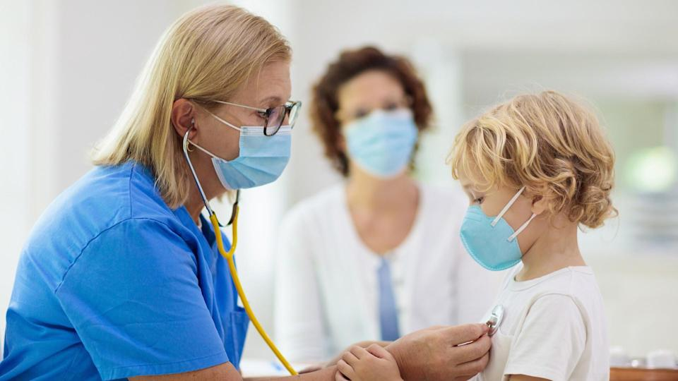 Pediatrician doctor examining sick child in face mask.