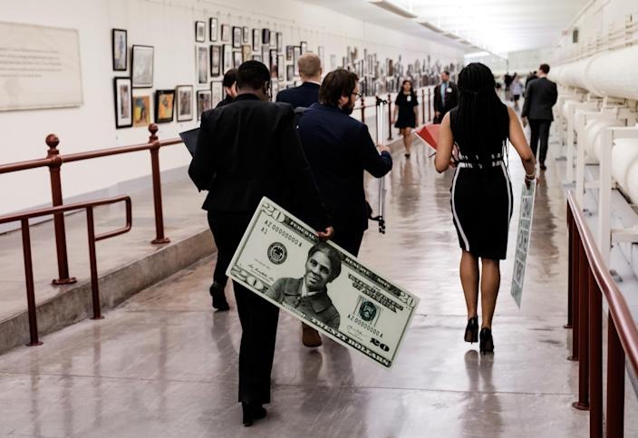 A congressional staffer departs holding a visual aide following a news conference regarding the redesigned $20 bill meant to honor Harriet Tubman.