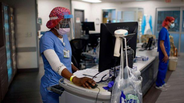 PHOTO: Registered respiratory therapist Niticia Mpanga reviews patient information in ICU at Oakbend Medical Center in Richmond, Texas, July 15, 2020. (Mark Felix / AFP via Getty Images)