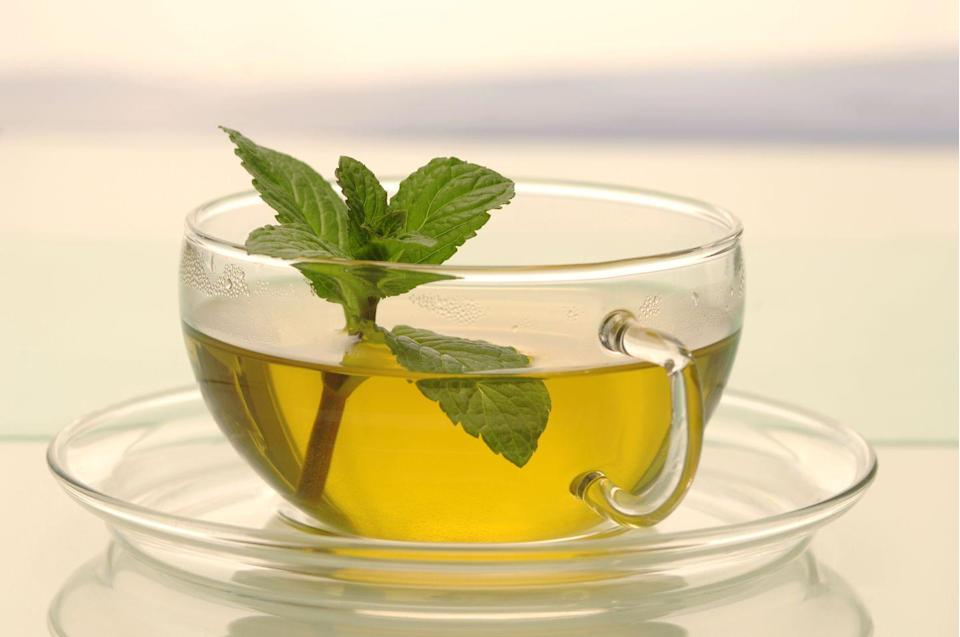 """<p>If you're feeling stretched out after a meal, do yourself a favor and reach for a steamy mug of mint tea. """"Oils in peppermint including menthol can help relax your GI muscles to relieve spasms that cause discomfort and your stomach to bloat,"""" Sumbal says.</p><p>She suggests steeping fresh peppermint tea leaves since the anti-bloat oils can be lost during the processing that occurs when mint is dried and then finely ground to stuff into tea bags. You can also toss fresh mint leaves into salads or mix with fruit.</p>"""