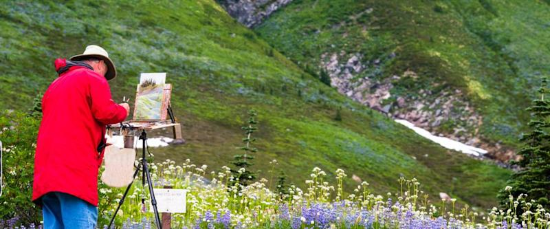 Artist outside in the field painting on his easel a landscape of the wildflowers in the mountains. Copy space.