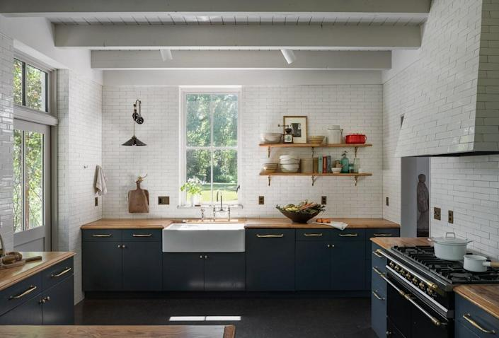 The kitchen features floor-to-ceiling tiles handmade in Portland. The sconce is by Hector Finch.