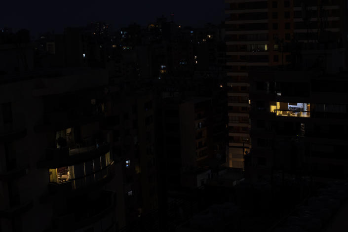 FILE - in this July 6, 2020 file photo, Lebanon's capital city of Beirut remains in darkness during a power outage. The multiple crises may seem like a standard summer in Lebanon, a country constantly vaulting from one disaster to the other. Only this time they come on top of financial ruin, collapsing institutions, hyperinflation and rapidly rising levels of poverty and unemployment. (AP Photo/Hassan Ammar, File)
