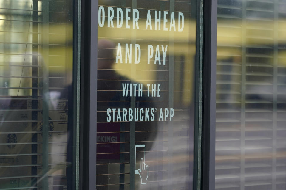 """A sign on a window at a Starbucks Coffee store in south Seattle reads """"Order ahead and pay with the Starbucks app,"""" Tuesday, Oct. 27, 2020. Starbucks saw faster-than-expected recovery in the U.S. and China in its fiscal fourth quarter, giving it confidence as it heads into the holiday season. (AP Photo/Ted S. Warren)"""