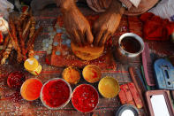 A Hindu priest prepares vermillion paste for pilgrims at Sangam during Magh mela festival, in Prayagraj, India. Friday, Feb. 19, 2021. Millions of people have joined a 45-day long Hindu bathing festival in this northern Indian city, where devotees take a holy dip at Sangam, the sacred confluence of the rivers Ganga, Yamuna and the mythical Saraswati. Here, they bathe on certain days considered to be auspicious in the belief that they be cleansed of all sins. (AP Photo/Rajesh Kumar Singh)