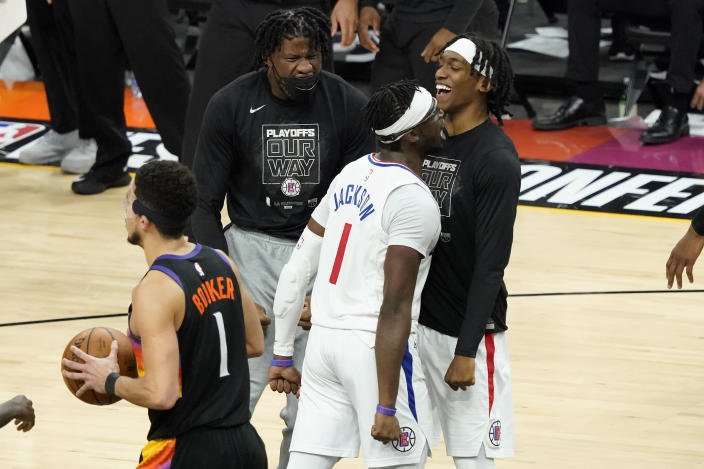 Los Angeles Clippers guard Reggie Jackson (1) celebrates a basket with teammates as Phoenix Suns guard Devin Booker (1) walks to his bench during the second half of game 5 of the NBA basketball Western Conference Finals, Monday, June 28, 2021, in Phoenix. (AP Photo/Matt York)